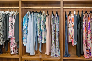 Colorful collection of women's clothes hanging in the wardrobe